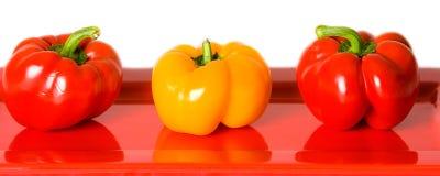 Rode en Gele Groene paprika's op een rode plaat. Royalty-vrije Stock Foto