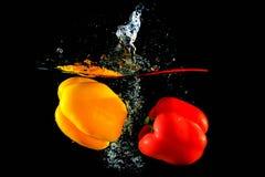 Rode en gele peper die in water vallen royalty-vrije stock fotografie
