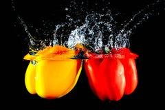 Rode en gele peper die in water vallen royalty-vrije stock afbeelding