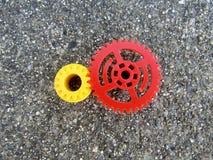 Rode en gele plastic tandraderen op asfaltachtergrond stock fotografie