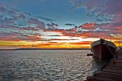 Rode en Gele zonsondergang met verlaten vissersboot royalty-vrije stock afbeelding