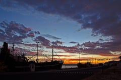Rode en Gele zonsondergang met vissersboten stock afbeelding