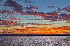Rode en Gele zonsondergang over brede rivier stock foto