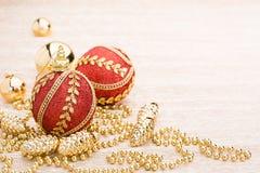 Rode en gouden Kerstmisbal op verlichte achtergrond stock afbeelding