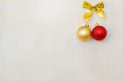 Rode en gouden Kerstmisballen die op houten achtergrond hangen Stock Foto