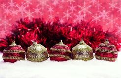 Rode en gouden Kerstmisballen in sneeuw met klatergoud en sneeuwvlokken, Kerstmisachtergrond Royalty-vrije Stock Afbeelding