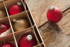 Rode en gouden Kerstmissnuisterijen in een doos Royalty-vrije Stock Afbeeldingen
