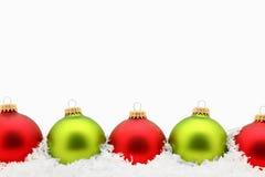 Rode en Groene Ornamenten in Sneeuw Stock Foto