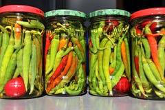 Rode en groene Spaanse peperspeper die in azijn wordt bewaard stock foto
