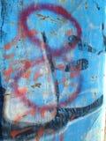 Rode en oranje graffiti op de blauwe geschilderde oude omheining Royalty-vrije Stock Foto