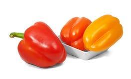 Rode en oranje klokpepers in horizontale positie inzake witte backg Stock Foto