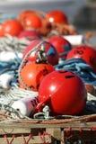 Rode en oranje vlotters op de pijler Stock Fotografie