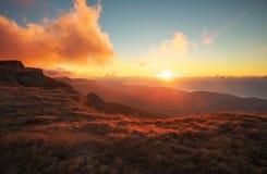 Rode en oranje zonsondergang in de bergen in de herfsttijd Royalty-vrije Stock Afbeeldingen
