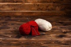 Rode en witte ballen van draad en breinaalden op een houten achtergrond stock foto's