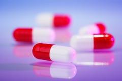 Rode en witte capsules (hap) op viooltje royalty-vrije stock foto