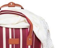 Rode en witte gestreepte bagagezak met een gebreide sweater op het, witte achtergrond, minimaal reisconcept met exemplaarruimte stock foto