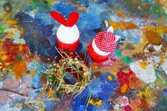 Rode en witte het konijntjeseieren van Pasen op oud kleurrijk artistiek houten palet stock fotografie