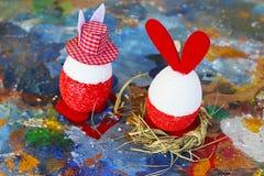 Rode en witte het konijntjeseieren van Pasen op oud kleurrijk artistiek houten palet stock foto