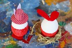 Rode en witte het konijntjeseieren van Pasen op oud kleurrijk artistiek houten palet royalty-vrije stock foto's