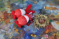 Rode en witte het konijntjeseieren van Pasen op oud kleurrijk artistiek houten palet stock afbeelding