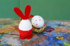 Rode en witte het konijntjeseieren van Pasen op oud kleurrijk artistiek houten palet royalty-vrije stock afbeelding