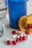 Rode en witte pillen, blauwe transparante container Stock Foto's