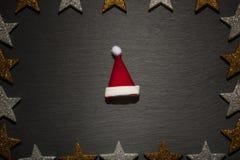 Rode en witte santahoed op lei met sterkader Stock Foto