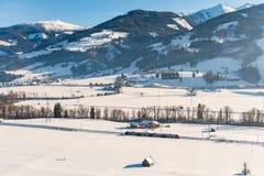 Rode en witte trein die de snow-covered gebieden in een toneellandschap van de de winterberg, Dachstein-massief, Liezen-District  stock foto