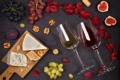 Rode en witte wijn met kaasplaat Wijnglazen met kaas, druiven, fig. en noten op zwarte achtergrond Royalty-vrije Stock Afbeeldingen