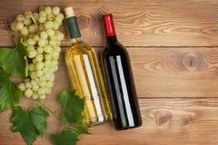 Rode en witte wijnflessen en bos van druiven Stock Afbeeldingen
