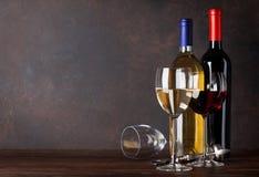 Rode en witte wijnflessen en glazen Stock Afbeeldingen