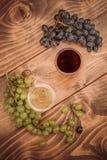 Rode en witte wijnglazen en druif op houten lijst Stock Foto's