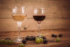 Rode en witte wijnglazen en druif op houten lijst Stock Afbeeldingen