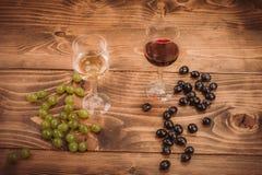 Rode en witte wijnglazen en druif op houten lijst Royalty-vrije Stock Fotografie