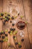 Rode en witte wijnglazen en druif op houten lijst Stock Fotografie