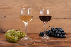 Rode en witte wijnglazen en druif op houten lijst Royalty-vrije Stock Foto