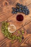 Rode en witte wijnglazen en druif op houten lijst Stock Afbeelding