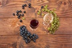 Rode en witte wijnglazen en druif op houten lijst Royalty-vrije Stock Foto's