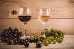 Rode en witte wijnglazen en druif op houten lijst Stock Foto