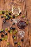 Rode en witte wijnglazen en druif op houten lijst Royalty-vrije Stock Afbeelding