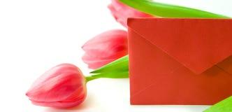 Rode envelop en een boeket van tulpen royalty-vrije stock afbeeldingen