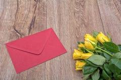 Rode envelop en rozen op een houten achtergrond Stock Afbeeldingen