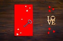 Rode envelop met harten en een sleutel op een houten achtergrond, c Stock Foto's