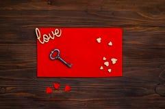Rode envelop met harten en een sleutel op een houten achtergrond, het concept de Dag van Valentine ` s, hoogste mening Stock Fotografie