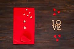 Rode envelop met harten op een houten achtergrond, het concept de Dag van Valentine ` s, bovenkant viewn Royalty-vrije Stock Afbeeldingen