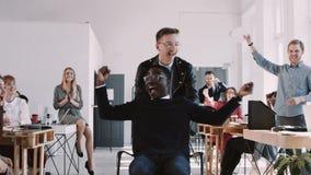 Rode episch-W Gelukkige pret gekke jonge Afrikaanse mannelijke beambte die carrière van succes genieten bij gezonde bureau langza stock video