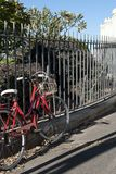 Rode fiets verlaten naast smeedijzeromheining stock afbeeldingen