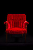 Rode fluweelstoel op zwarte achtergrond Royalty-vrije Stock Foto's
