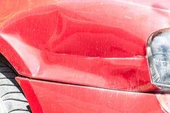 Rode gekraste auto met beschadigde verf in neerstortingsongeval op de straat of parkeerterrein in de stad Stock Afbeeldingen
