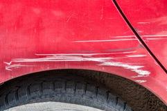 Rode gekraste auto met beschadigde verf in neerstortingsongeval op de straat of parkeerterrein in de stad Stock Fotografie